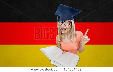 people, national education, knowledge and graduation concept - smiling young student woman in mortarboard and eyeglasses with encyclopedia book pointing finger up over german flag background