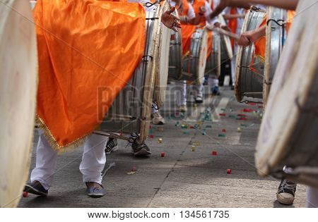 Traditional percussion instruments caled Dhol been played uring a Ganesh festival procession in India.