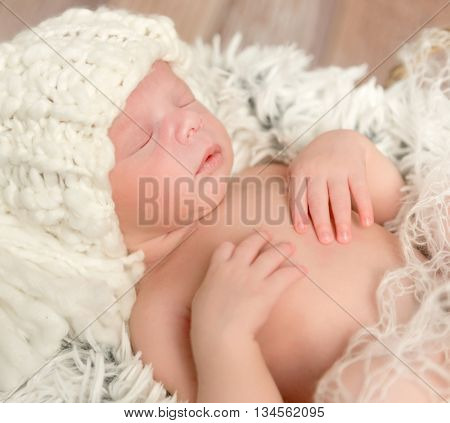lovely face of newborn baby in knitted white hat lying on fur