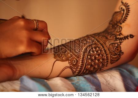 An artist making traditional design with beautiful patterns of henna or mehendi on the hands of an Indian bride.