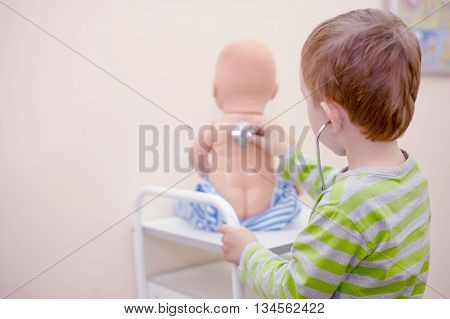 kid playing doctor with a stethoscope. boy playing with a doll and treats it. view from the back. copy space for your text