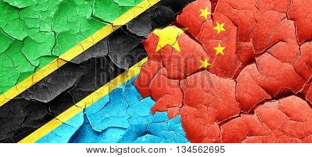 Tanzanian flag with China flag on a grunge cracked wall