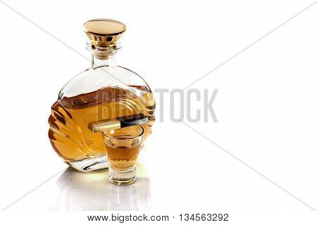 Bottle and a shot glass of tequila with chocolate on a white background