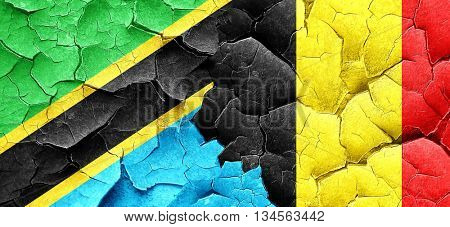 Tanzanian flag with Belgium flag on a grunge cracked wall