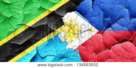 Tanzanian flag with Philippines flag on a grunge cracked wall