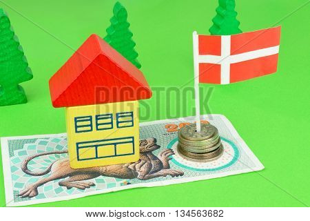 A toy house on a Danish Kroner note with a flag and coins.