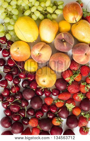 Fresh mixed fruits and berries.Fruits, berries background.Healthy eating, dieting.Love fruits, clean eating. Grape, lemons, apricots, peaches and plums and strawberies and cherry.colorful background