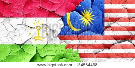 Tajikistan flag with Malaysia flag on a grunge cracked wall