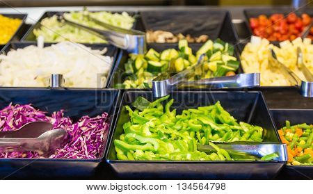 Fresh vegetables in stainless steel containers in a salad bar