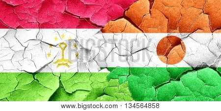 Tajikistan flag with Niger flag on a grunge cracked wall