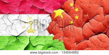 Tajikistan flag with China flag on a grunge cracked wall