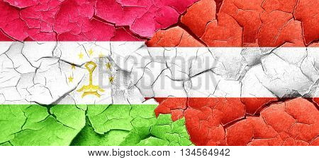 Tajikistan flag with Austria flag on a grunge cracked wall