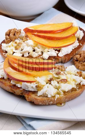 Sandwich of oat bread with ricotta and slices of peach nuts watering honey
