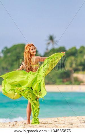 young beautiful woman dancing on sand beach in tropics, vacation vitality healthy living concept