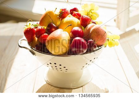 Fresh mixed fruits, berries in bowl. Love fruit, berry. Fruits, berries in bowl in sunlight near the window. Healthy eating, dieting. Summer food, clean eating.