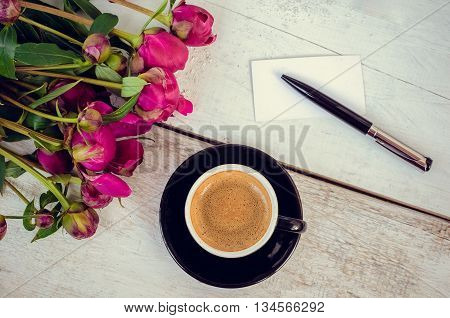 A cup of coffee and pink flowers Peonies on a wooden table with an empty card for text and pen. Breakfast on Mothers day, Valentines Day or Womens day. Writing greetings card. Copy space. Top view.