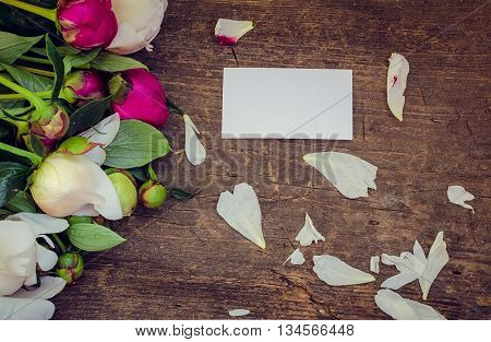 Peony background. Fuchsia, pink and white peonies on old wooden table with an empty card for text. Happy Mothers Day. Mother's Day greetings card. Valentines Day. Copy space.