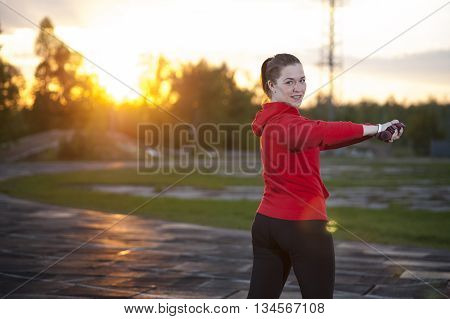 Young woman in red hoody and black leggings doing exercise with dumbbells. Fitness workout and sport outdoors