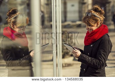 Beautiful young girl standing next to a shop window and typing a text message on her tablet computer