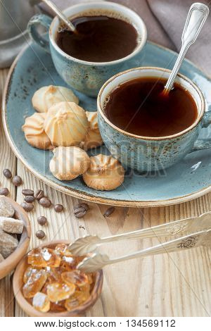 Two blue cups of black coffee biscuits and sugar pieces surrounded by linen cloth and sugar-tongs on old wooden table