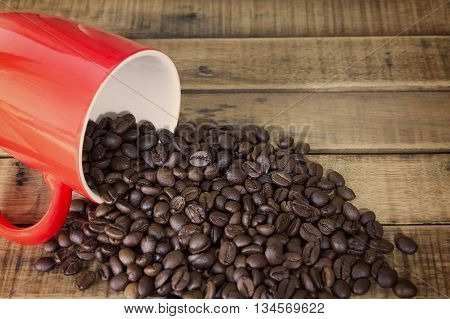 coffee beans and red cup on the wooden table background.