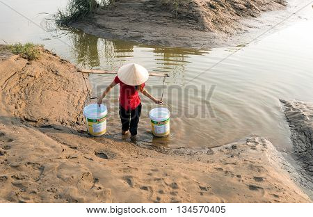 HA NOI, VIET NAM, April 29, 2015 the woman, a suburb of Ha Noi, Vietnam, carrying water from the river Hong