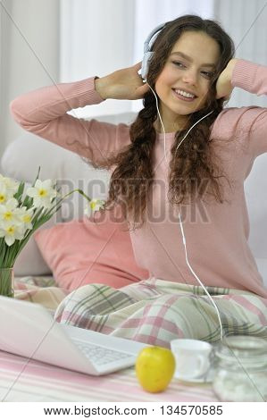 Attractive young woman inn headphones using laptop