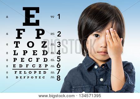 Close up portrait of little Asian boy reviewing eyesight. Kid closing one eye with hand and alphabetical eye test chart in background.