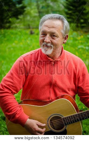 Portrait of a handsome senior man in bright sweater looking at the camera and plays acoustic guitar outdoor. Smiling happy senior man with gray hair and beard. Outdoors. Vertical image.