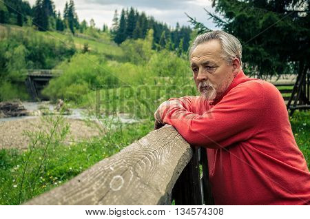 Portrait of a handsome senior man in bright sweater relying on the wooden fence near the river in the mountines and thinking . Serious senior man with gray hair and beard. Horizontal image.