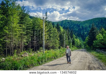 Full length portrait of a handsome senior man in the beautiful place. Looking at the camera. Serious senior man with gray hair and beard on the mountains road. Horizontal image.