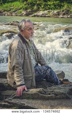 Portrait of a handsome senior man sitting in beautiful place near the river waterfall in the mountains and thinking. Serious senior man with gray hair and beard. Combination with nature.