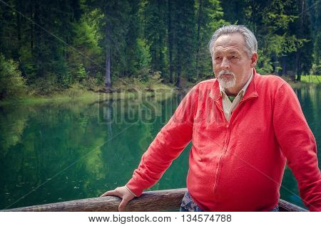 Portrait of a handsome senior man in bright sweater near the beautiful forest lake. Looking far away. Serious senior man with gray hair and beard on excursion. Horizontal image.