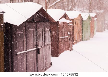 Line of colorful garages at winter snowfall. Abstract winter background/