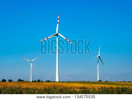 Wind turbine electric power generators in the filed in Austria on blue sky