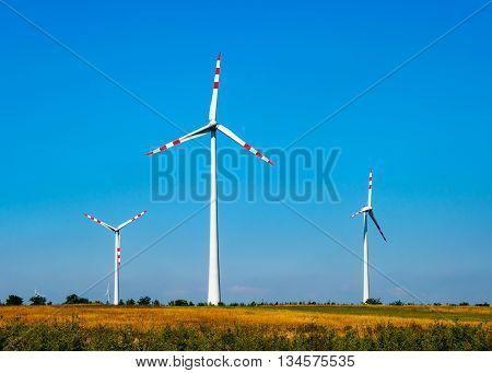 Wind turbine electric power generators in the filed in Austria on blue sky