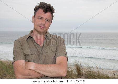 Handsome man standing on the beach and looking thoughtfully into the distance