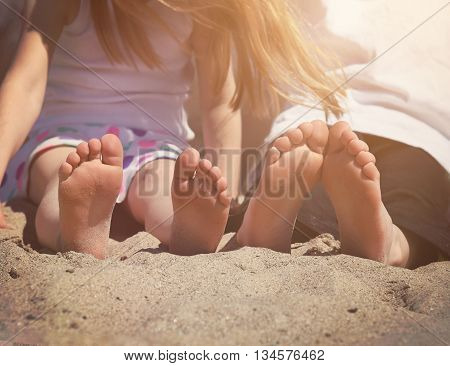 Children are sitting on a sand beach with their bare feet together for a vacation travel or summer concept