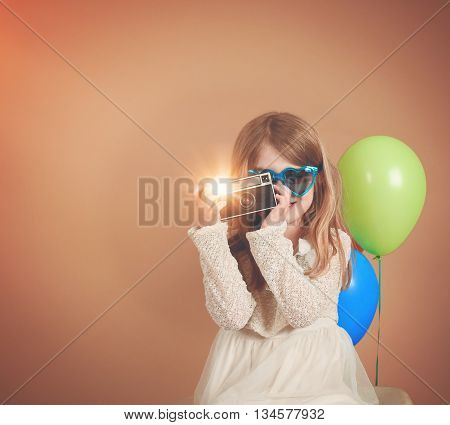 A photo of a vintage child taking a picture with an old camera against a blank wall with balloons for a creativity or vision concept.