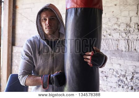 Portrait Of Young Male Boxer With Punch Bag In Gym