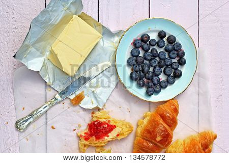 Delicious breakfast with fresh croissants and ripe berries on old wooden background selective focus