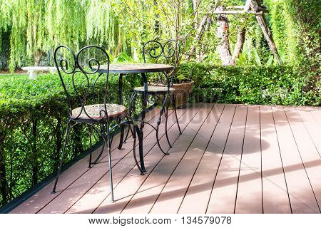 Black chair in the garden for relax. Green garden and patio terrace in house. Classic garden with black chair on patio terrace in house.