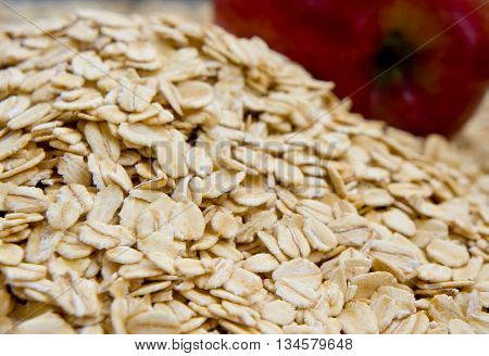 grits are scattered on a surface, rounded shape the processed grains, near a heap of crude grain red apple lies, one