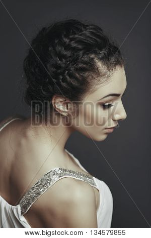 Side face portrait of beautiful female fashion model posing with braided hairdo wearing white low cut blouse looking down over grey background.