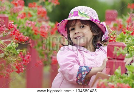 The little girl close in a pink hat and a raincoat. green background. Sweet toddler girl on red bridge