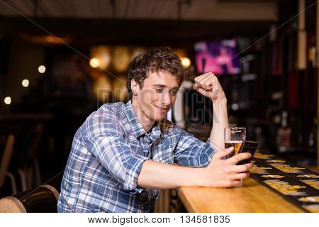 Single Man Sitting At Bar Having A Beer