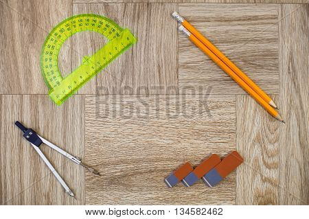 Pencil, Eraser, Circinus And Protractor Ruler On A Wooden Texture