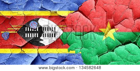 Swaziland flag with Burkina Faso flag on a grunge cracked wall