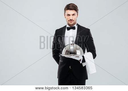 Attractive young waiter in tuxedo holding serving tray with metal cloche and napkin