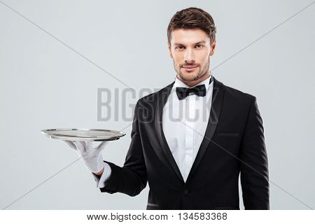 Portrait of young butler in tuxedo holding empty tray
